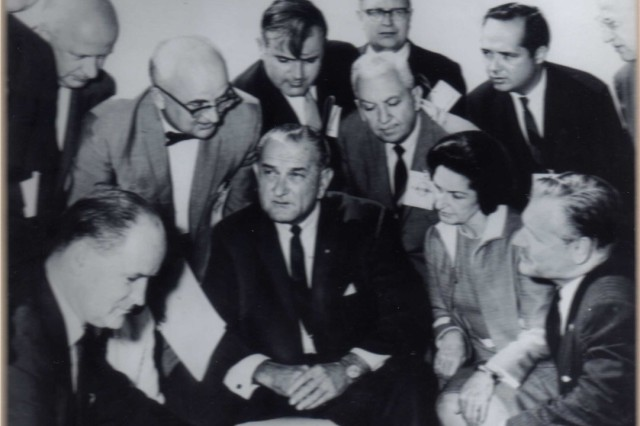 New York Governor Nelson Rockefeller and Lady Bird Johnson (lower right) look on as Stan (left, glasses and bow tie) lobbies a stern-faced LBJ.