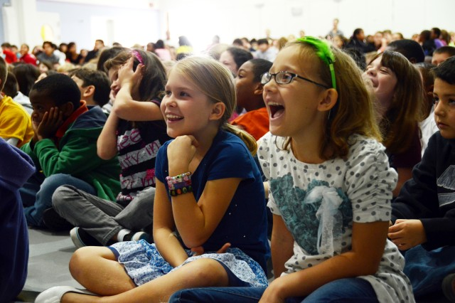 Alyssa Houchsell, 8, (left) and Morgan Bisahap, 8, laugh along with their classmates during Trevor Romain's motivational show at Netzaberg Middle School, Oct. 18.