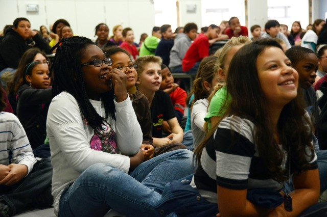 Shatiara Woodley, 9, (left) and Alyssa Martinez, 9, giggle along one of the Trevor Romain's videos during his Oct. 18 visit to Netzaberg Middle School. The video addressed cliques and deployment in a funny, accessible way that held the students' attention, even while teaching them.