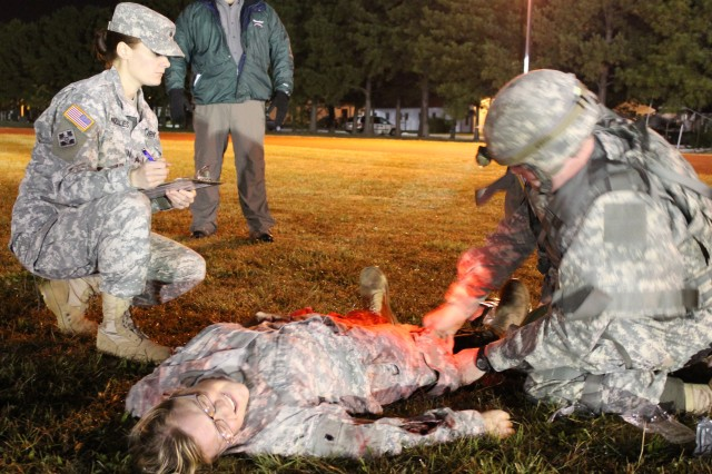 Sgt. Laura Gonzales, Kenner Army Health Clinic medic evaluates a Best Warrior competitor during the Department of the Army Solider and Noncommissioned Officer of the Year Best Warrior Competition event. Thirteen KAHC medics supported the casulaty evaluation event,