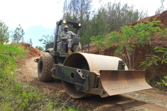 "Spc. Dale Correia, , heavy equipment operator for the 523rd Engineer Company, 84th Engineer Battalion, 130th Engineer Brigade, 8th Theater Sustainment Command, operates the roller for the finishing work after re-shaping a broad-based diversion ditch on the ""driver's training course"" at the East Range on Schofield Barracks."