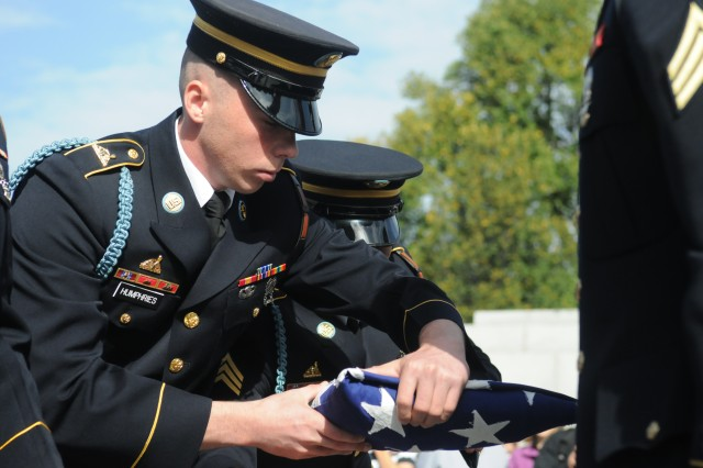 Spc. Jeremiah Humphries passes a flag to Sgt. Timothy Goeres, both infantrymen with Honor Guard Company, 3d U.S. Infantry Regiment (The Old Guard), during a flag folding ceremony at the World War II Memorial in Washington, D.C., Oct. 20, 2012. The flag was the original used during a funeral in the 1940's for a World War II veteran who died in the war. Eighty-seven World War II and Korean War veterans visited the memorial with the help of the Honor Flight Network, a non-profit organization which transports veterans of past wars to their respective memorials in Washington, D.C.