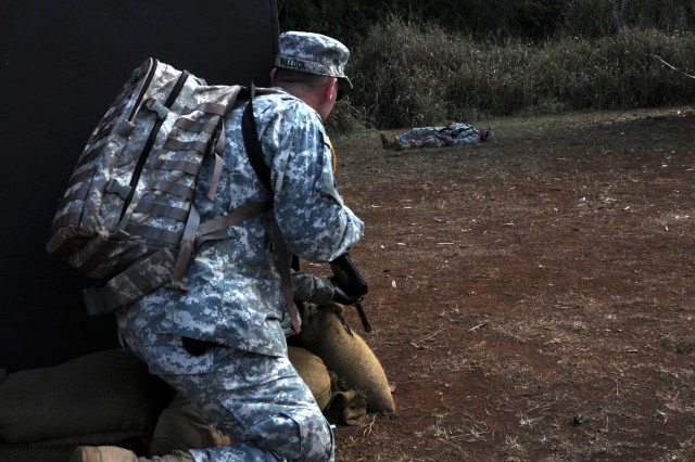 Staff Sgt. Jason Bullock, optician, Tripler Army Medical Center, and an evaluator for the upcoming U.S. Army Pacific Expert Field Medical Badge testing, prepares to enter a mock field of fire tactical combat lane to help an injured Soldier during lane validation rehearsal, here, 22 Oct.