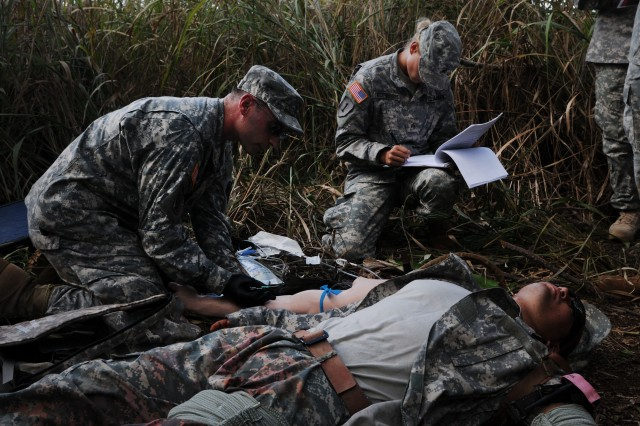 Staff Sgt. Jason Bullock, optician, Tripler Army Medical Center, and an evaluator for the upcoming U.S. Army Pacific Expert Field Medical Badge testing, helps an injured Soldier and prepares to start an IV in a mannequin arm in a mock combat tactical lane, as a group of evaluators and a test board panel evaluates him, during lane validation rehearsal, here, 22 Oct.