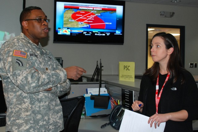 Maj. Dennis Martinez, a plans officer for the New York National Guard discusses reporting procedures for emergency response with Laura Aery, an intelligence analyst with the office of counterterrorism. Both are working as liaisons at the New York State Office of Emergency Management Operations center representing their agencies preparing to respond to Hurricane Sandy, Oct. 26, 2012.