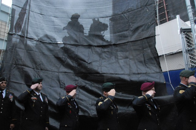 U.S. Army Special Operations Command Soldiers salute during the singing of the National Anthem, shadowed by the iconic Horse Soldier Statue during the re-dedication of what is now called the America's Response Statue, Oct. 19, Ground Zero Memorial plaza, New York City.