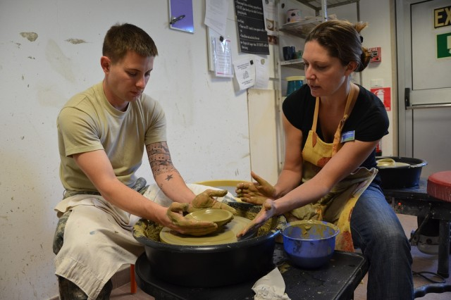 Michelle Sterkowicz, Supervisory Arts Specialist, shows Spc. Kevin Taylor, Warrior Transition Unit, how to use the pottery wheel during Resiliency through Art class Oct. 23 at the Vicenza Family and MWR Arts and Crafts Center.