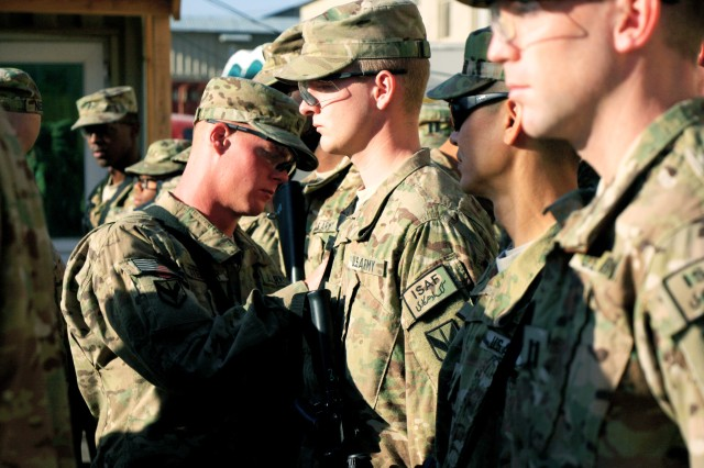 Spc. Paul Stelzer pins the 1st Sustainment Brigade combat patch onto Pvt. Chris Griffin's right shoulder during the 1st Special Troops Battalion Patching Ceremony at the 1st Sustainment Brigade headquarters at Bagram Airfield, Oct. 12.