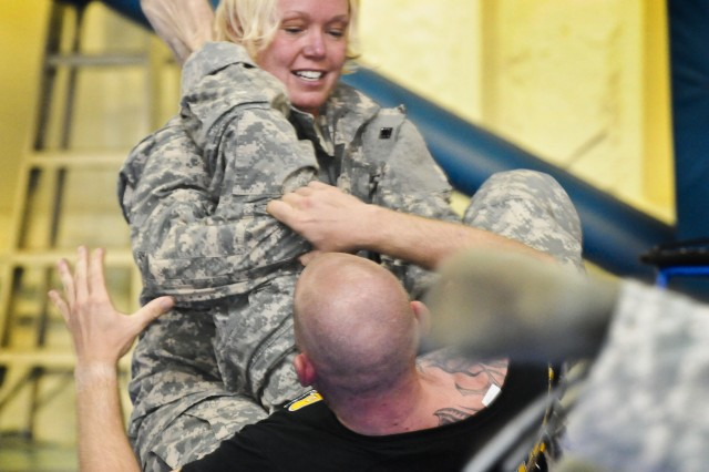 Capt. Marsha Reveal goes after Sgt. 1st Class Travis Nargang's leg during the Army Sustainment Command's Level 1 Modern Army Combatives training at the Rock Island Arsenal Community Fitness Center, Oct. 1, on Rock Island Arsenal, Ill. (Photo by Sgt. 1st Class Sean Riley, ASC Public Affairs)