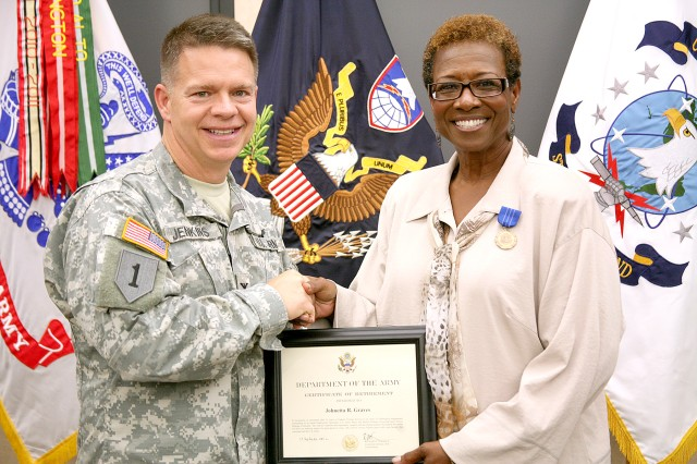 Col. James Jenkins, chief of staff, U.S. Army Space and Missile Defense Command/Army Forces Strategic Command, presents Johnetta Graves, an equal employment opportunity manager with the command, with a certificate of retirement during Graves' ceremony at the command's Redstone Arsenal headquarters Oct. 25. Graves retires with 35 years of service.