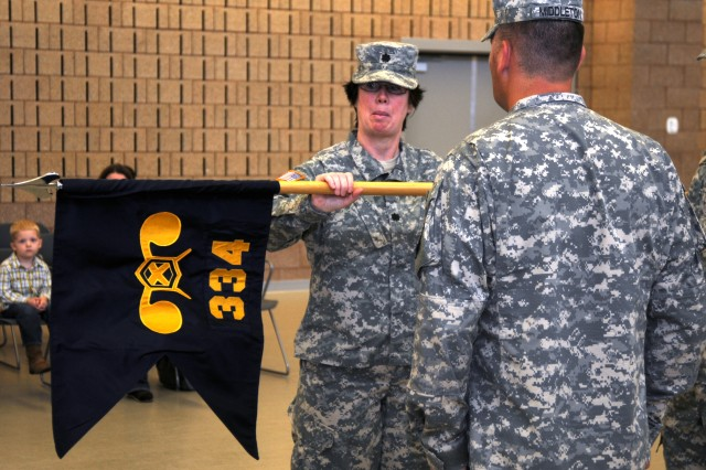 Lt. Col. Molly Young, commander of the 453rd Chemical Battalion, unfurls the colors of the 334th Chemical Company at its activation ceremony, Oct. 27, 2012. The 334th Chemical Company is a U.S. Army Reserve unit based in Marysville, Wash.