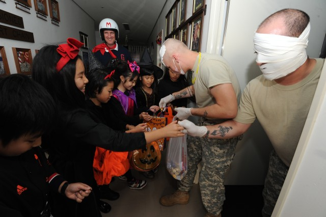 35th Combat Service Support Battalion soldiers hand out candy to students from LCA Kokusai Elementary School while 'Speed Racer' costumed Lt. Col. Joseph O. Ritter, commander of the 35th CSSB, escorts during the Friendship Halloween event at Sagami General Depot Oct. 29.