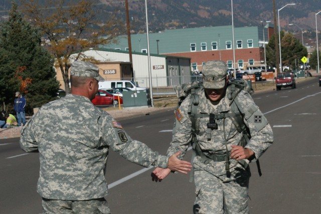 """FORT CARSON, Colo. """" First Lieutenant Matthew Zamperini (right), fire support officer, Company B, 1st Squadron, 10th Cavalry Regiment, 2nd Brigade Combat Team, 4th Infantry Division, high fives Sgt. 1st Class Spencer Polwart, brigade fire support element noncommissioned officer in charge, Headquarters and Headquarters Troop, 2nd Special Troops Battalion, 2nd BCT, 4th Inf. Div., as he crosses the finish line of a 12-mile ruck march Oct. 18, 2012. The ruck march was the final task in completing recertification. Soldiers had to complete 12 miles in three hours or less to pass."""