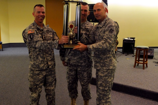 """FORT CARSON, Colo. """" Major General Joseph Anderson (right), commanding general of 4th Infantry Division and Fort Carson presents a trophy to Lt. Col. Dave Guthrie (center), commander, and Command Sgt. Maj. Brian Vogel, senior enlisted leader, both of 1st Squadron, 10th Calvary Regiment, 2nd Brigade Combat Team, 4th Inf. Div. for their squadron achieving the highest overall score during the fire support team recertification and competition, at Fort Carson's Veteran Chapel, Oct. 26, 2012. The recertification and competition took place Oct. 15 thru 18 with Soldiers being evaluated on a written test, a physical fitness test, land navigation, a call for fire test and a 12-mile ruck march."""