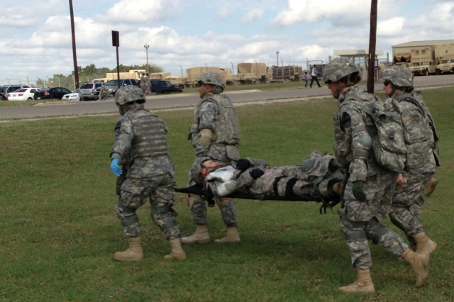 """FORT HOOD, Texas """" Union, Mo. native, Pfc. Christina Garcia (back-left), combat medic assigned to C Co. 115th BSB, 1st BCT, 1st Cav. Div., assists a dummy-casualty during Expert Field Medical Badge training, here, Oct. 25."""