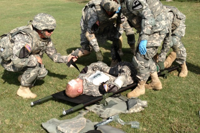"""FORT HOOD, Texas """" Union, Mo. native, Pfc. Christina Garcia (wearing blue gloves), a combat medic assigned to C Co. 115th BSB, 1st BCT, 1st Cav. Div., assists a dummy-casualty during Expert Field Medical Badge training with her evacuation platoon, here, Oct. 25."""