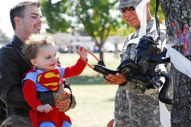 FORT HOOD, Texas -- A young child dressed as Superman tosses a ring during the Spider Ring Toss of the 1st BCT, 1st Cav. Div.'s Trunk or Treat, here, Oct. 27.
