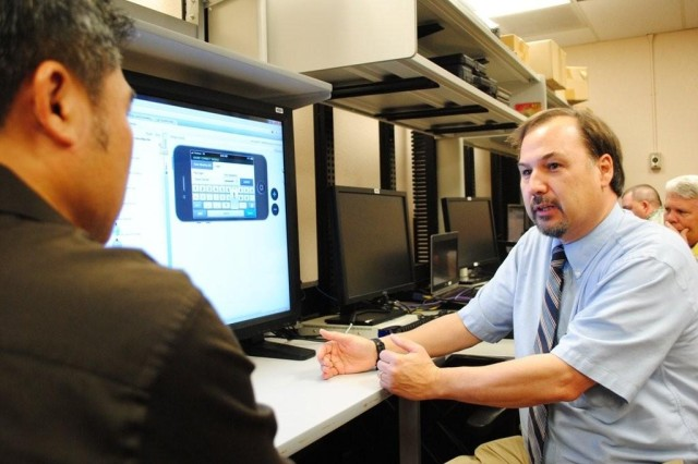 John LeCompte, Defense Information Systems Agency mobility instrumentation lead for the Joint Interoperability Test Command, speaks with Tuan Nguyen, contract senior system engineer at JITC, during a demonstration of a test tool for mobile devices on Oct. 2. DISA, JITC's higher headquarters recently embraced mobility as part of its Strategic Plan. Supporting this initiative is JITC, as the Joint Chiefs of Staff charged the organization with testing and evaluating technology and communications systems for joint use.