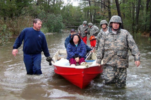 Virginia National Guard Soldiers transport citizens through high water to reach their medium tactical truck for evacuation on Cattail Road in the Mears, Va., area, Oct. 30, 2012.