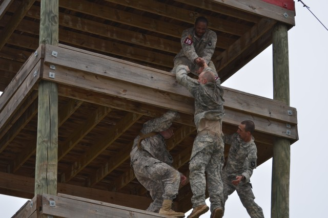 Sgt. Marcus Freeman, 101st Airborne Division (Air Assault), Fort Campbell, Ky. helps his teammate, Cpl. Brandon Borchers, master one of many obstacles Oct. 26 at Joint Base San Antonio-Camp Bullis.
