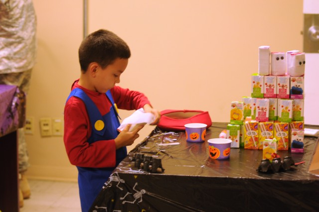 A boy dressed as a superhero makes a juice box mummy at the 5th Armored Brigade's Halloween Spooktacular held Oct. 24 at Fort Bliss, Texas. (Photo by Capt. John A. Brimley, 5th Armored Brigade, Division West, Public Affairs)