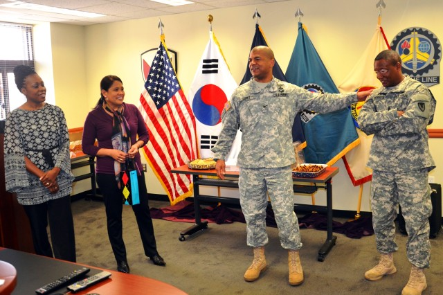Col. Michael Lopez, commander, 403rd Army Field Support Brigade, and his wife, Marianne (next to him), welcome the new 403rd AFSB Command Sgt. Maj. Dexter Speights, and his wife, Wonda (far left), to the 403rd AFSB. (Photo by Pfc. Kim Joon Hyung, 403rd AFSB)
