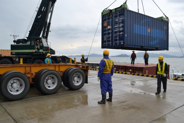 Japanese master labor contractors move a container from a barge to the docking area at Hiro Army Depot, Kure, Japan. The 83rd Ordnance Battalion, headquartered in Kure, currently operates the depot. The unit will inactivate in 2013.
