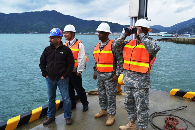 Command Sgt. Maj. Shelton Williamson, command sgt. maj., 10th Regional Support Group, gets a closer look at a ship in the ocean with binoculars as Command Sgt. Maj. Lenoard Pitts, command sgt. maj., 83rd Ordnance Battalion, looks on. The 83rd Ordnance, headquartered in Kure, Japan is set to inactivate next year.