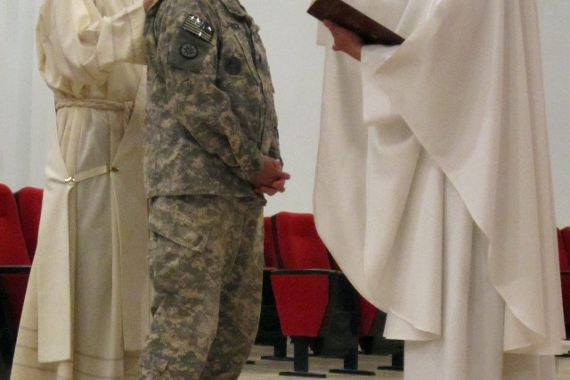 "1st Lt. Denny Black is welcomed into the Catholic Church by ARCENT Chaplain (Maj.) Rajmund Kopec, right, and Maj. Marcus Salazer, left, during mass at Camp Arifjan, on Oct. 31.  ""Chaplain Kopec explained the process to me and conducted some one-on-one counseling concerning my spiritual journey,"" Black explained.  Celebrating mass in here was a fitting location for Black, ""I was married by an Army Chaplain in 1989, renewed my wedding vows by an Army Chaplain in 2012, so it was only fitting that I conduct my religious conversion with an Army Chaplain."""