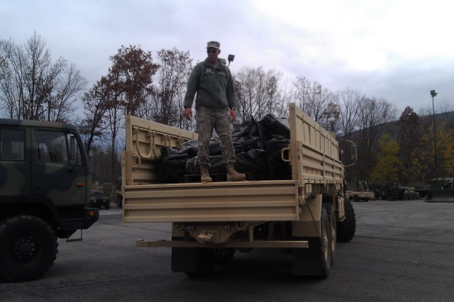 Spc. Jerry Barton, Army Reserve Soldier with the 327th QM Company out of out of Williamsport, Penn., assist Soldiers from the 401st QM Team out of Lock Haven, Penn., as the units prepares to support Hurricane Sandy relief efforts.