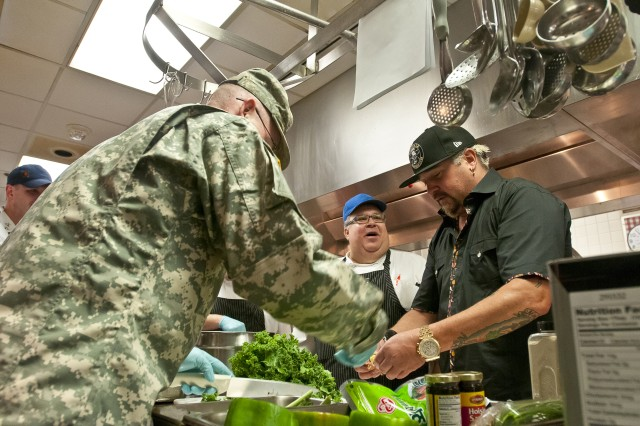 Famed TV chef and New York Times best selling cookbook author Guy Fieri prepares chicken tetrazzini with Spc. Christopher Lauber (left), the production and service noncommissioned officer for Madigan Army Medical Center's dining hall on Joint Base Lewis-McChord, Wash., and one of its cooks, James Lowery Jr., during a visit to the hospital Nov. 3. Fieri was filming at local eateries in Seattle, Puyallup and Olympia for his show, Diners, Drive-Ins and Dives, when he stopped in to cook with the kitchen's staff and meet with Soldiers from the installation's Warrior Transition Battalion.