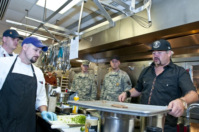 Famed TV chef and New York Times best selling cookbook author Guy Fieri prepares Salisbury steak alongside cooks at Madigan Army Medical Center's dining hall on Joint Base Lewis-McChord, Wash., during a visit to the hospital Nov. 3. Fieri was filming at local eateries in Seattle, Puyallup and Olympia for his show, Diners, Drive-Ins and Dives, when he stopped in to cook with the kitchen's staff and meet with Soldiers from the installation's Warrior Transition Battalion.