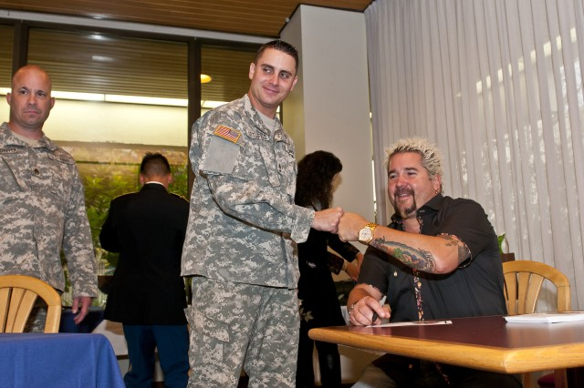 Famed TV chef and New York Times best selling cookbook author Guy Fieri poses for a photo with Sgt. 1st Class Gabriel Littlefield at Madigan Army Medical Center on Joint Base Lewis-McChord, Wash., during a visit to the hospital Nov. 3. Fieri was filming at local eateries in Seattle, Puyallup and Olympia for his show, Diners, Drive-Ins and Dives, when he stopped in to cook with the kitchen's staff and meet with Soldiers from the installation's Warrior Transition Battalion.