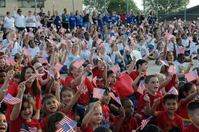 About 725 Nolanville Elementary students, ranging from pre-kindergarten to 5th grade, dressed in red, white and blue formed the letters U.S.A. on the school's basketball court and waved flags to welcome an AH-64D Longbow Apache helicopter and its crew in the early morning, Oct. 25, 2012, at Nolanville Elementary School, Texas.