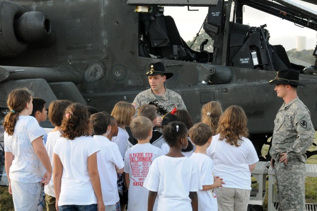 Apache pilots, Maj. Joseph Bishop and Maj. Ryan Atkins, 21st Cavalry Brigade (Air Combat), answer questions from students about the AH-64D Longbow Apache helicopter during Science Day at Nolanville Elementary School, Texas, Oct. 25, 2012.