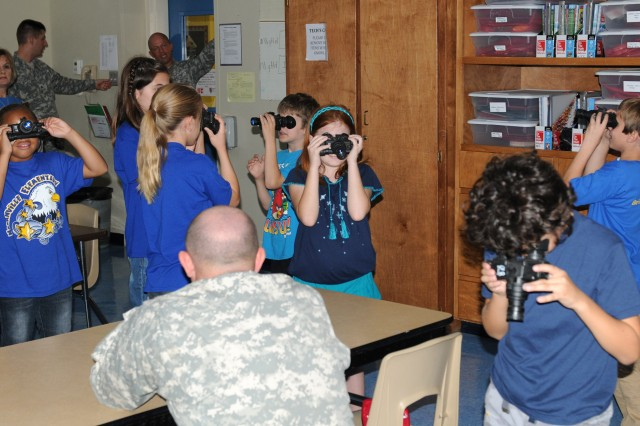 Students from Nolanville Elementary School wear night vision goggles during a class instructed by Soldiers from the 615th Aviation Support Battalion, 1st Air Cavalry Brigade, 1st Cavalry Division, during Science Day held at Nolanville Elementary School, Texas, Oct. 25, 2012.