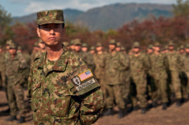 An officer of the Japan Ground Self Defense Force listens to remarks during the closing ceremonies of Orient Shield 12.  He proudly displays patches he received from Soldiers with the 1st Battalion, 14th Infantry Regiment, during the previous night's dinner.  Bilateral training between the two forces took place at the Aibano Training Area near Imazu City, Japan, Oct. 24 - Nov. 7, 2012.