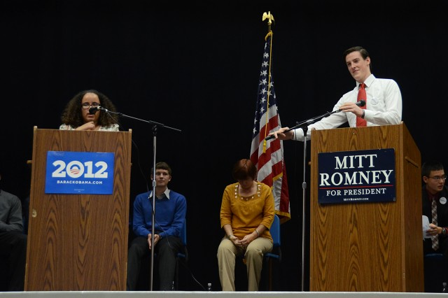 Kendy Espinal (left) and Kevin Huestis, campaign managers for the Obama and Romney campaign, respectively, give their closing statements during a mock presidential debate at Vilseck High School, Nov. 1.