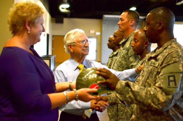 Sylvia James, the widow of Lt. Col. Leon James, a former battalion commander for the 2/314th Field Artillery Battalion who was killed in Iraq in 2005, and Leon Tartar, the last known World War II survivor of the 79th Reconnaissance Troop, present a World War II helmet signed by the members and family members of the 79th Reconnaissance Troop and the 314th Infantry Regiment to noncommissioned officers representing 157th Infantry Brigade, First Army Division East.