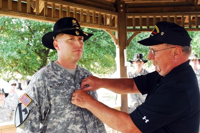 FORT HOOD, Texas -- Retired Sgt. Maj. Brian Kielpinski (right) promotes his son Lt. Col. Michael Kielpinski (left), commander of 1-9 Cav, 4th BCT, 1st Cav. Div. during a ceremony here, Oct. 23.