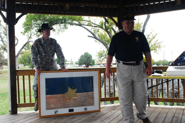 "FORT HOOD, Texas -- Retired Sgt. Maj. Brian Kielpinski (right) talks about his Cavalry pride as he donates a North Vietnamese Army flag, lighter, and belt buckle he captured during his tour in Vietnam to the troopers of 1-7 Cav ""GarryOwen"", 1st  BCT, 1st Cav. Div., here Oct. 23."