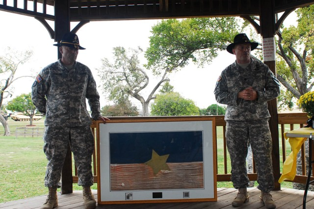"FORT HOOD, Texas -- Lt. Col. Jay Miseli (right), commander of 1-7 Cav ""GarryOwen"", 1st BCT, 1st Cav. Div. and Command Sergeant Maj. William Burford, accept a North Vietnamese Army flag, lighter, and belt buckle donated by former B Company, 1-7 Cav Soldier, Sgt. Maj (Ret.) Brian Kielpinski, here Oct. 23. Kielpinski captured the items during his 1967 to 1968 Vietnam tour."