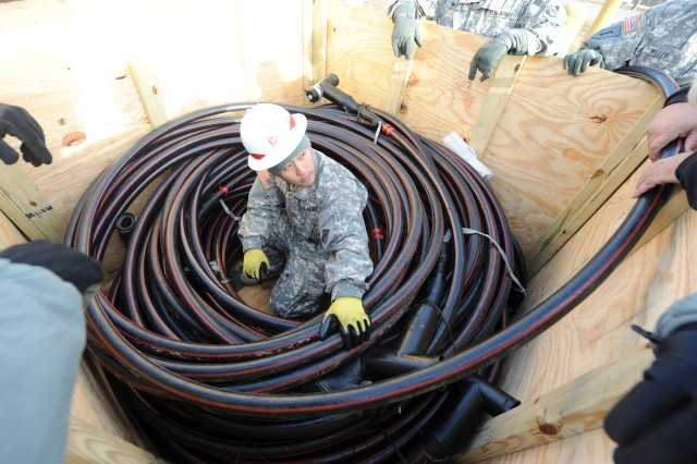 Sgt. Muy Thor inspects a large generator cable before installing it at a fuel depot in Carteret, N.J., Nov. 6, 2012. Thor and other Soldiers from the 249th Engineer Company (Prime Power), installed generators to supply power to the depot, which lost power during Hurricane Sandy.
