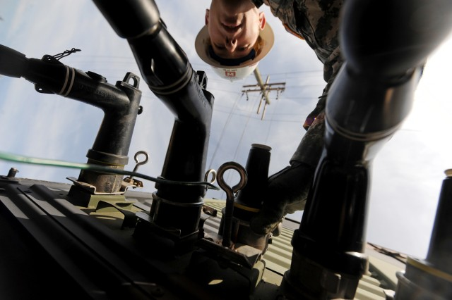 Sgt. George Miller of the 249th Engineer Battalion (Prime Power), attaches cables to a generator being supplied to a fuel depot without power in Carteret, N.J., Nov. 6, 2012. Hurricane Sandy knocked out power, which helped cause fuel rationing in the state.