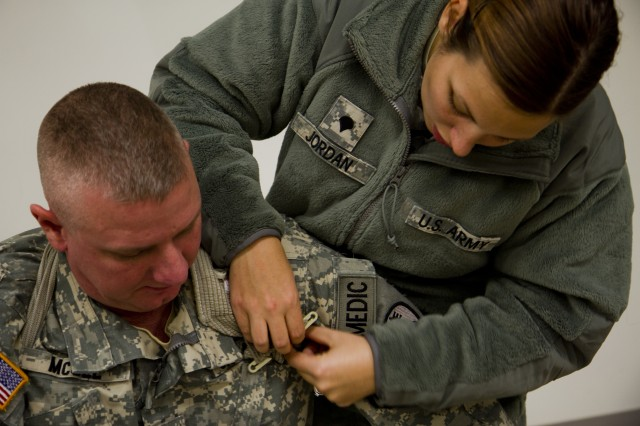 Spc. Stevi Jordan, a medic assigned to the 342nd Military Police Company in Columbus, Ohio, practices applying a field bandage on Sgt. Michael McGee, a medic with the 342nd, at the Medical Simulation Training Center on Fort McCoy, Wis. Oct. 27, 2012. Jordan, a native of Laurelville, Ohio, and McGee, a native of Zanesville, Ohio, are attending a 72-hour course that will allow them to maintain their Military Occupation Specialty requirements. (Army Reserve photo by Spc. Jacquelyn R. Slaughter)