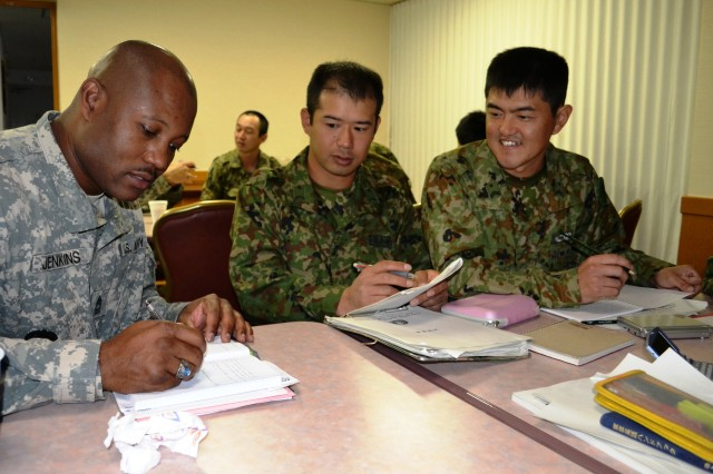 Master Sgt. Kevin Jenkins, battalion maintenance supervisor, 83rd Ordnance Battalion, helps his Japanese counterparts from the 46th Inf., 13th Bde., JGSDF, during an English calss at the 83rd Ord. Bn. headquarters in Kure, Japan.