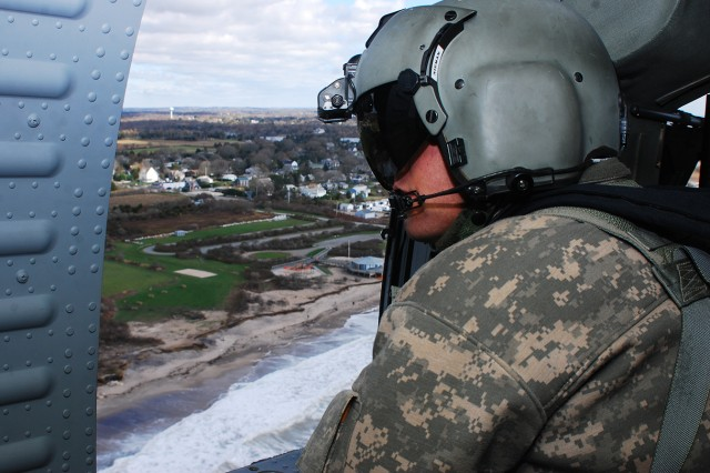 Spc. Gabriel J. Nieman, a UH-60 Black Hawk helicopter crew chief with 3-10 General Support Aviation Battalion, Task Force Phoenix, 10th Combat Aviation Brigade, looks out at the southern Rhode Island coastline, Nov. 1, 2012. Two UH-60 Black Hawks transported Federal Emergency Management Agency Region II representatives to assess damage along the coast.