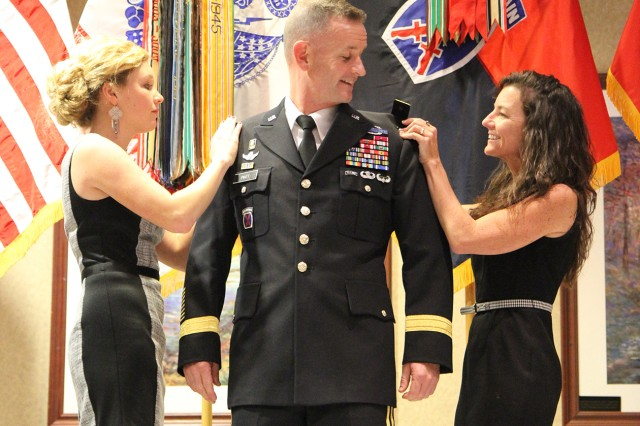 Brig. Gen. Walter E. Piatt's wife, Cynthia, right, and daughter, Jessica, pin his shoulder boards during his promotion ceremony Friday on post.