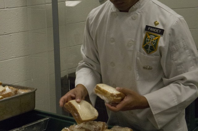 Spc. Bishal Pandey, a cook assigned to the 200th Military Police Command at Fort Meade, Md., places ham and cheese sandwiches into shallow pans here Nov. 3, 2012. Pandey, a native of Silver Spring, Md., helps prepare lunch for the 200th MPCOM Soldiers during battle assembly weekend. (Army Reserve photo by Spc. Jacquelyn R. Slaughter)