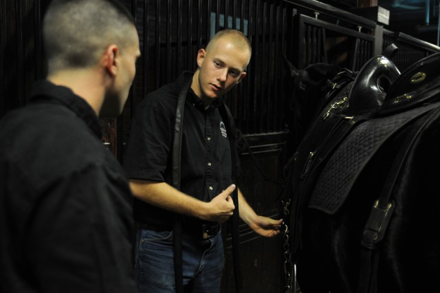 Spc. Dmitry Malkov, infantryman, Caisson Platoon , 3d U.S. Infantry Regiment (The Old Guard, trains a Soldier on how to prepare and  maintain horse equipment at the Caisson horse stables on Joint Base Myer - Henderson Hall, Va., Oct. 18. The Old Guard offers Soldiers who join specialty platoons, like the Caissons, opportunities that are unavailable anywhere else in the Army. (U.S. Army photo by Sgt. Luisito Brooks)